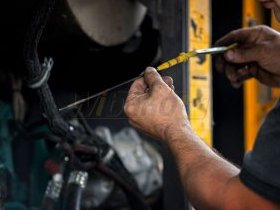 Sprawdzanie stanu oleju silnikowego w maszynie budowlanej