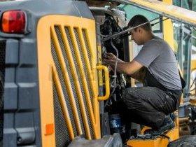 Mechanik w trakcie prac serwisowych przy maszynie budowlanej